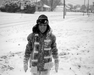A child pausing from his play in the snow to pose for a picture